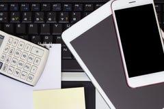 Räknemaskin, smartphone och minnestavla på bärbar datortangentbordet, affärsidé arkivfoton