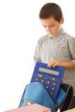 räknemaskin som sätter schoolbagschoolboyen royaltyfri bild
