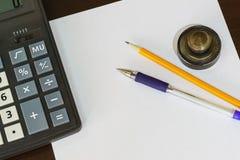 Räknemaskin, tryck, penna och blyertspenna som ligger på ett tomt ark av papper Fotografering för Bildbyråer