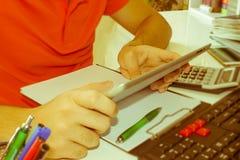 Räknemaskinerna, ipaden, företagsägarna, redovisningen och teknologin, affären, datoren, räknemaskinen och dokumenten i kontoret Arkivbild