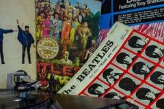 Räkning av det berömda Beatles Abbey Road albumet med en skivtallrik i förgrunden royaltyfria bilder