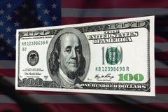 räkning för dollar 100 på en bakgrund av USA-flaggan Royaltyfria Bilder