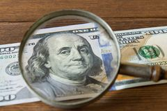 räkning för dollar 100 under ett förstoringsglas på en trätabell _ Arkivbild