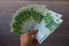Räkningar av hundra euro i en hand på en träbakgrund arkivfoto