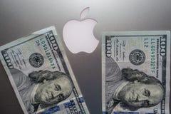 $100 räkningar mot den Apple logoen royaltyfri bild