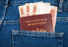 Räkningar och passet för rysk rubel i jeansen stoppa i fickan Arkivfoto