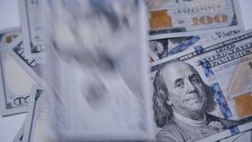 Räkningarna av 100 dollar som faller på roterande bakgrund 4K arkivfilmer