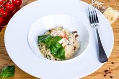 Räkor med ris på en vit platta med gaffeln på träbakgrund Risotto med höna, champinjoner och parmesan arkivfoto