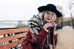 Rätselhafte Frau im Ruhestand, die auf Spazierstock sich lehnt stockfoto