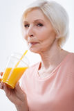 Rätselhafter recht blonder trinkender frischer Orangensaft Lizenzfreies Stockbild