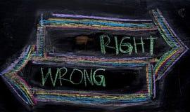 Rätt eller orätt som är skriftliga med färgkritabegrepp på svart tavla royaltyfri foto