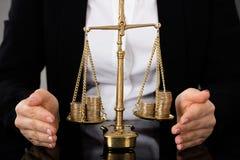 Rättvisa Scale With Coins för hand för advokat` s skyddande arkivbilder