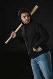 Räuber im zoodie mit Baseballschläger und Geld lokalisiert auf Schwarzem Lizenzfreie Stockfotos