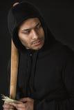 Räuber im zoodie mit Baseballschläger und Geld lokalisiert auf Schwarzem Lizenzfreies Stockfoto