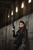 Räubermädchen im Lederkostüm mit einer Armbrust an der Beitrag-apokalyptischen Welt Stockfotos