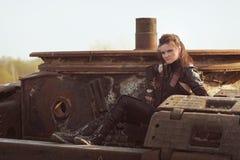Räubermädchen im Lederkostüm mit einer Armbrust an der Beitrag-apokalyptischen Welt Stockbilder