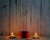 Räucherstäbchen mit Kerzenflamme auf hölzernem Hintergrund Stockfoto