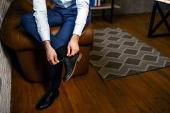 Rżnięty widok młody przystojny biznesmen w jego swój biurze Trzyma nogę na inny jeden i wiąże koronki na butach ruchliwie zdjęcie royalty free