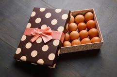 Rå ägg i en halv öppen gåvaask på svart bakgrund royaltyfri foto
