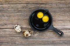 Rå ägg i panna på gammal träbakgrund Royaltyfri Foto