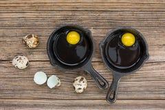 Rå ägg i stekpanna, vaktelägg på träbakgrund Arkivfoto