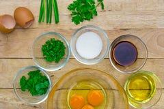 Rå ägg och ingredienser på träbakgrund Arkivbild