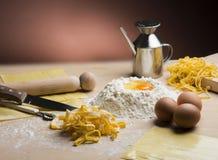 Rå äggpasta med mjöl och kavlen Royaltyfria Bilder