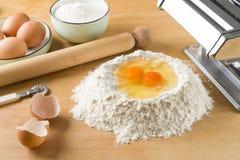 Rå äggpasta med mjöl och kavlen Royaltyfria Foton