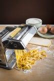 Rå äggpasta med mjöl och kavlen Arkivbilder