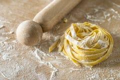 Rå äggpasta med mjöl och kavlen Arkivbild