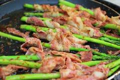 Rå bacon slogg in grön sparris i stekpanna på mörk backgrou royaltyfria foton