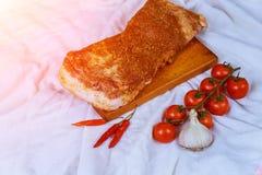 Rå baconskivor och träbunkar med torra kryddor det vita brädet på den bruna vita bakgrunden Royaltyfri Fotografi