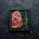 Rå biff för öga för nötköttstöd med rosmarin på bästa sikt för svart bakgrund Fyrkantig kantjustering royaltyfria foton