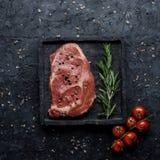 Rå biff för öga för nötköttstöd med tomater och rosmarin på bästa sikt för svart bakgrund Fyrkantig kantjustering royaltyfri bild
