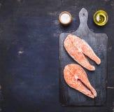 Rå biff två till laxen, skaldjur, sund mat med örter, persilja, olivolja och den salta mörka tappningskärbrädan på trärus Royaltyfri Fotografi