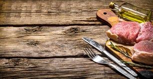 Rå biffar på det gamla brädet med olja, kniven och gaffeln Royaltyfria Foton