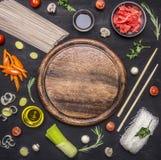 Rå bovetenudlar med grönsaker, ingefära, pinnar och ingredienser som ut läggas runt om skärbrädastället för text, ram Royaltyfri Foto