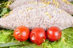 Rå bröad fiskkotlett med körsbärsröda tomater för sallad Royaltyfri Foto