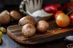 Rå champinjoner på träbräde Tre champinjoner på kök Arkivfoton