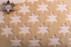 Rå deg för julkakor för barn som gör pepparkakakakor i formen av snöflinganärbilden cutting arkivfoton