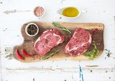 Rå för Ribeye för nytt kött entrecôte och smaktillsatser biff på skärbräda över vit träbakgrund Royaltyfri Foto