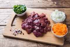 Rå feg lever för att laga mat med grönsaker arkivfoton