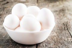 Rå fega vita ägg i den vita bunken på träbakgrund Arkivfoto