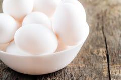 Rå fega vita ägg i den vita bunken på träbakgrund Royaltyfri Bild