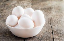 Rå fega vita ägg i den vita bunken på träbakgrund Royaltyfria Foton