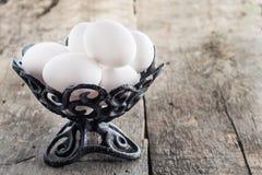 Rå fega vita ägg i en järnantikvitetvas Arkivfoton