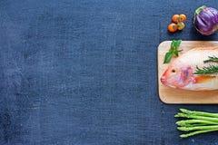 Rå fisk och grönsaker på en mörk tabell royaltyfria bilder