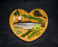 Rå fisk på hjärta format bräde royaltyfri bild