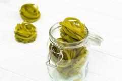 Rå grön tagliatellepasta på en glass krus Fotografering för Bildbyråer