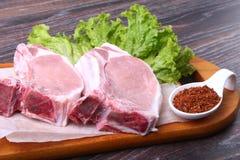 Rå grisköttbiff med kryddor lämnar grönsallat på träskärbräda Ordna till för att laga mat Arkivfoto